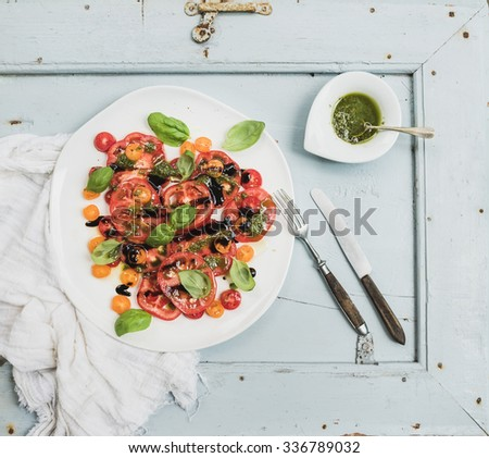 Ripe village heirloom tomato salad with olive oil and basil over light blue wooden background, top view - stock photo