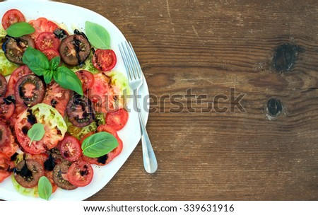 Ripe village heirloom tomato salad with olive oil and basil over rustic wooden background, top view, copy space - stock photo