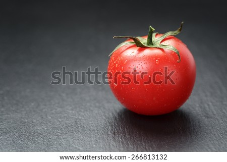 ripe washed tomato on slate background - stock photo