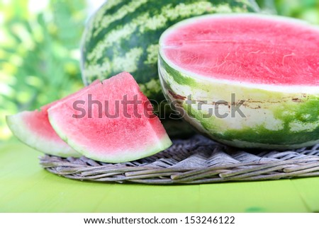 Ripe watermelons on wicker tray on wooden table on nature background