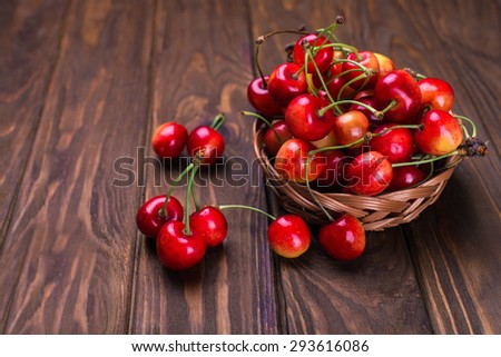 Ripe yellow and red cherries on wooden table with in a basket - stock photo