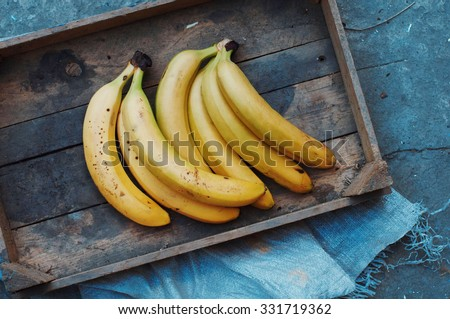 ripe yellow bananas in wicker basket,  on wooden background, view from above, yellow fruits, yellow bananas in a wooden box, food, meal, vitamins, - stock photo