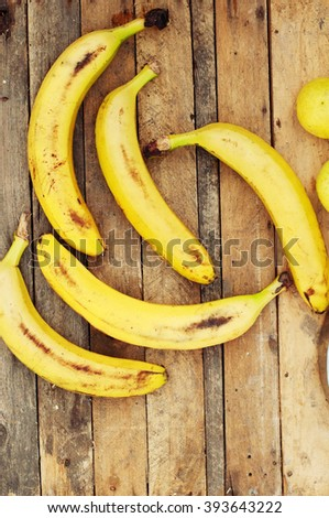 ripe yellow bananas in wicker basket, on wooden background, view from above, yellow fruits, yellow bananas in a wooden box, food, meal, vitamins - stock photo