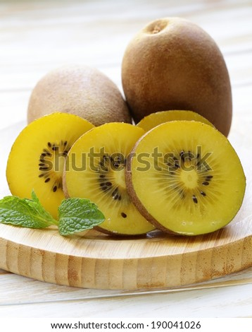 ripe yellow kiwi on a wooden board - stock photo