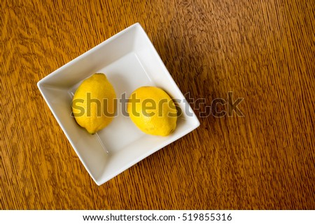 Ripe yellow lemons in a bowl over wood.