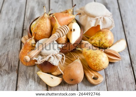 Ripe yellow pears and jars of honey on old wooden background