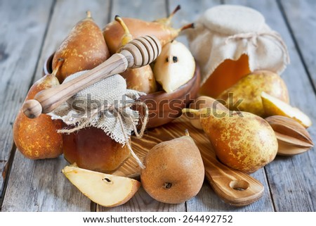 Ripe yellow pears and jars of honey on old wooden background - stock photo