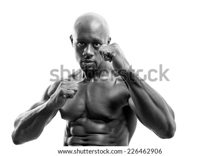 Ripped and muscular martial artist holding his fists up in black and white. Great boxing or fitness concept. Shallow depth of field. - stock photo