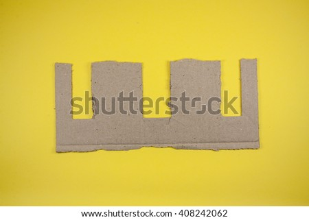 Ripped cardboard on yellow background - stock photo