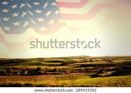 Rippled US flag against scenic landscape - stock photo