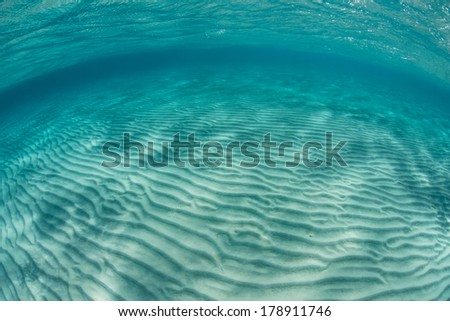 Ripples of sand run across a shallow flat in the warm waters of the Caribbean Sea. - stock photo