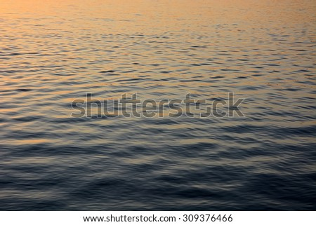 Ripples on the blue water at the sunset. Background, texture. - stock photo
