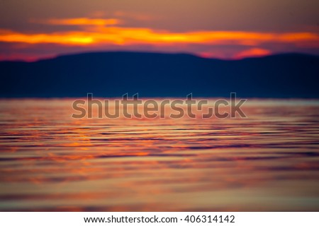 Rippling water surface close up details with shallow depth of field in orange sunset reflected over lake Balaton, Hungary - stock photo
