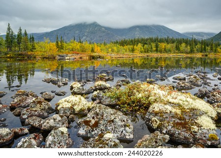 Rischorr mountain with peak hidden in clouds reflected in shallow Polygonal northern taiga forest lake with lichen-covered rocks in foreground - stock photo