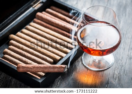 Rising aroma of burnt cigar and cognac - stock photo