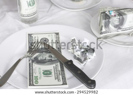 Rising food prices, high cost of living concept, eating foot made out of money - fake hundred dollar bills - stock photo
