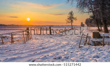 Rising sun over Winter Landscape with Snowy Fields and Blue Sky in Drenthe Netherlands