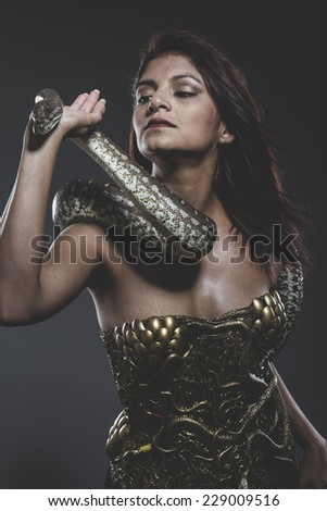 Risk, Sensual tattooed woman with big snake and iron corset - stock photo