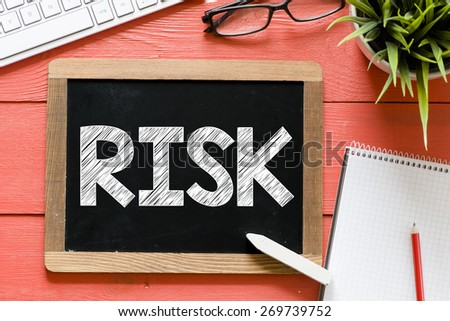 Risk word Handwritten on blackboard. Risk word Handwritten with chalk on blackboard, keyboard,notebook,glasses and green plant on wooden background - stock photo