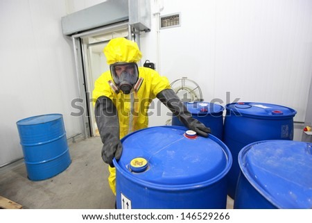 risky job - technician in protective uniform rolling barrel with toxic substance in plant