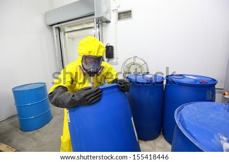 risky job - technician in protective uniform rolling barrel with toxic substance in plant  - stock photo