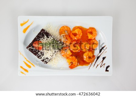 Risotto of brown rice with a slice of tomato and shrimp in tomato sauce