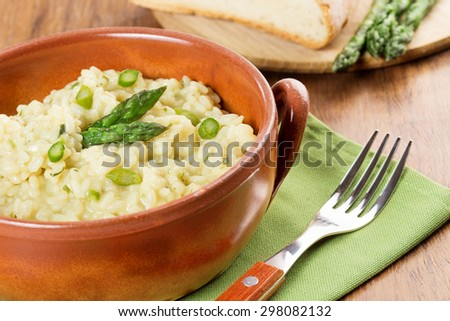 risotto with asparagus in a terracotta bowl over a green napkin - stock photo