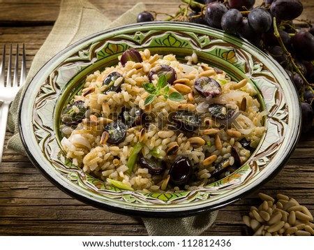 risotto with mushroom grape and pine cone, vegetarian food - stock photo