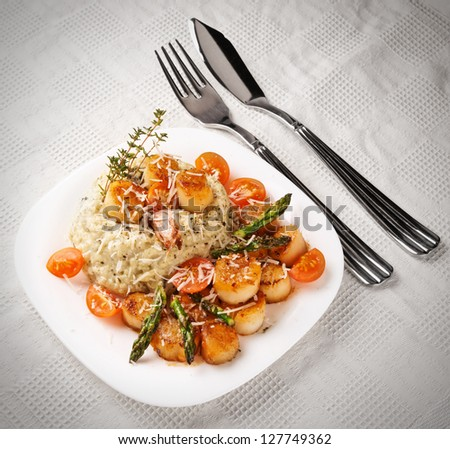 Risotto with pan seared sea scallops on table with old style vignetting - stock photo