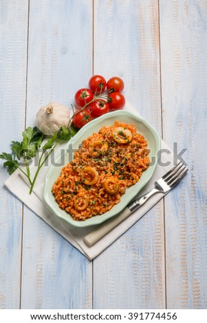 risotto with squid tomato and parsley - stock photo