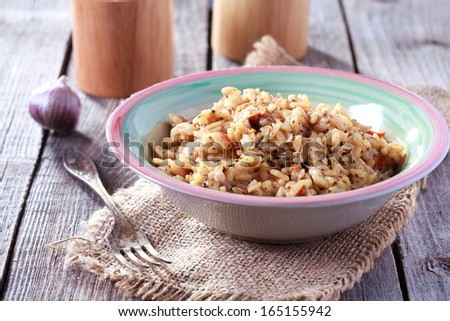 Risotto with sun-dried tomatoes and dried basil in a rustic style - stock photo