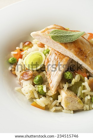 Risotto with vegetable and chicken served on white plate close up - stock photo