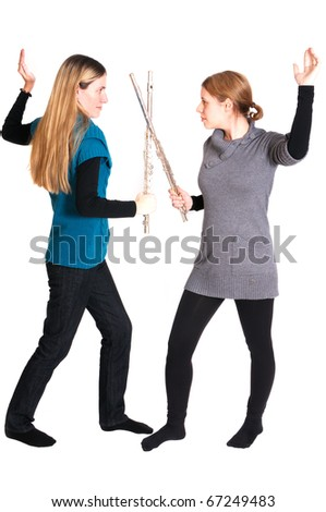 Rivalry between two young women with transverse flute isolated on white background. - stock photo