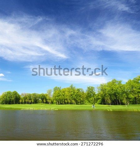 River and the green lawn, man riding a bicycle by the grass. Blue sky above the trees in spring day