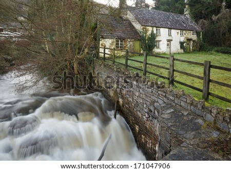River Angidy in Spate, with old cottages, Tintern - stock photo