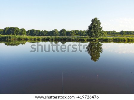 River bank. Fishing. Rod and float in water - stock photo