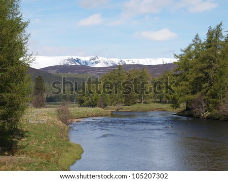 River Dee  east of Braemar with the snow covered Cairngorms mountain in the background, Scotland.