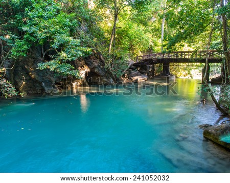 River flowing through from Erawan waterfall in deep forest of national park, Thailand with a bridge background - stock photo