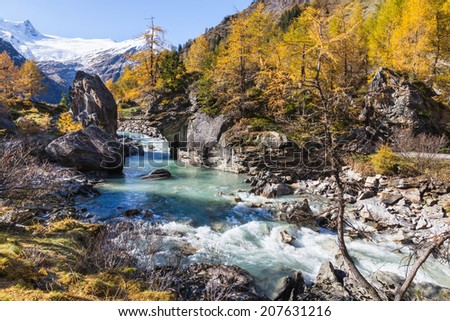 River in alp landscape at autumn - stock photo