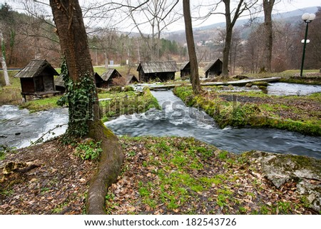 River in the forest with built wooden water mills in the popular ancient village near city Jajce in Bosnia and Herzegovina.  - stock photo