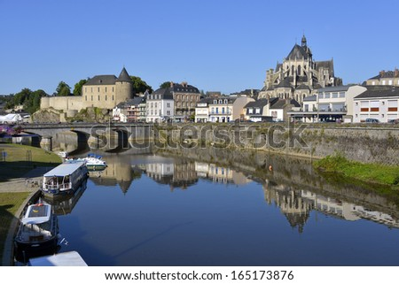River in the town of Mayenne with Notre-Dame basilica and the castle, commune in the Mayenne department in north-western France - stock photo