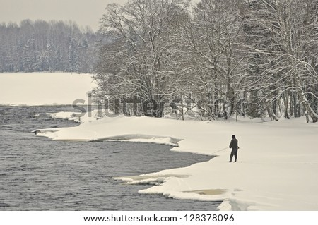 River in winter and a fisherman - stock photo