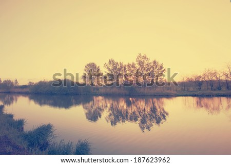 river landscape with sunset against ripple water - vintage retro style - stock photo