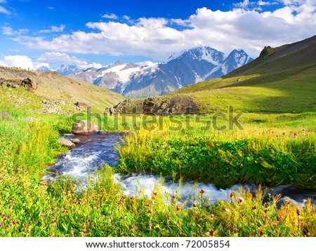 River on meadow in mountain valley. Natural composition