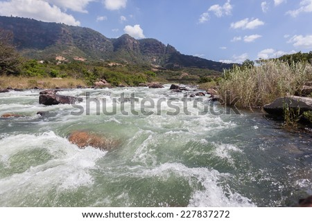 River Rapids Water Valley River rapids rocks and fast flowing water power and energy of nature through tropical valley - stock photo