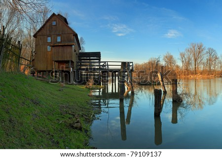 River reflection with watermill and tree - stock photo