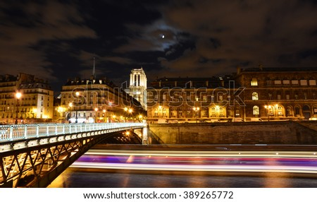 River Seine night view with Notre Dame cathedral in the background - stock photo