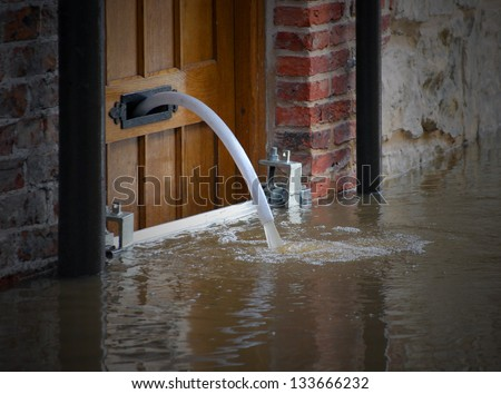 River water being pumped out of flooded house - stock photo