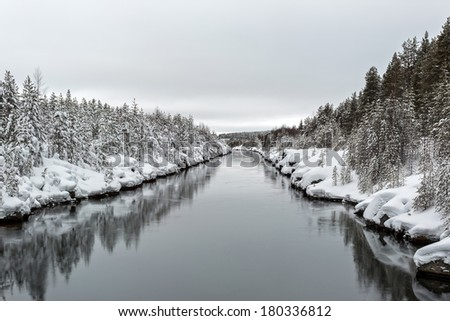 River with ice and snow and trees in Sweden - stock photo
