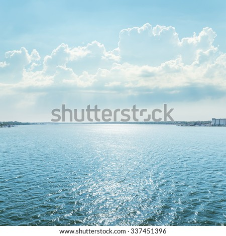 river with reflections of sun under blue sky with clouds - stock photo
